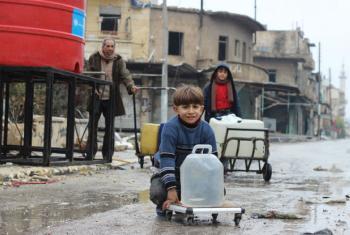 Homem e crianças carregam águas coletadas em ponto de distribuição apoiado pelo Unicef no leste de Alepo. Foto: Unicef/Khuder Al-Issa