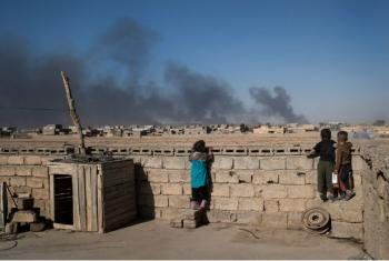 No topo de suas casas, srianças olham fumaça de poços de petróleo incendiados por integrantes do grupo terrorista Isil quando deixaram a cidade de Qayyarah, no sul de Mossul (arquivo). Foto: Unicef/Mackenzie