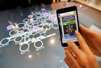 """Um dos participantes da Conferência joga o """"Hive Mind 2030"""" no celular durante o Festival Global de Ideias para o Desenvolvimento Sustentável, em Bonn, na Alemanha. Foto: photothek/Ina Fassbender"""