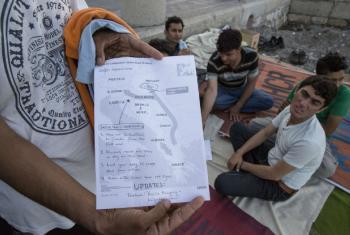 Migrantes paquistaneses em Kos, na Grécia, mostram um mapa que eles receberam com informações sobre o fechamento da fronteira da Hungria. Foto: OIM