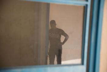 Um jovem aguarda em um centro de trânsito da OIM em Agadez, no Níger. Ele e seu irmão mais novo decidiram retornar a seu país de origem depois ter tentado ir à Europa e não ter conseguido. Foto: OIM 2016/Amanda Nero