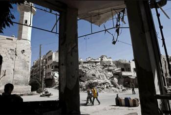 Meninos passam por prédios destruídos na cidade de Maarat al-Numaan, na Síria. Foto: Unicef/Giovanni Diffidenti
