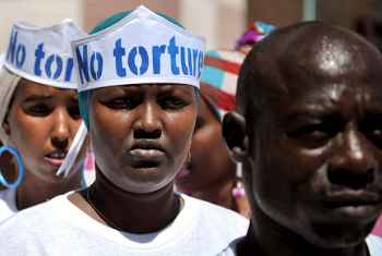 """Somalis com chapéus com inscrição """"Não à tortura"""" em evento do Dia dos Direitos Humanos no exterior da Cadeia Central de Mogadíscio. Foto: ONU/ Tobin Jones."""