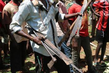Comandante da milícia anti-Balaka recolhe armas entregues por crianças em uma cerimônia em Bambari, na República Centro-Africana. Foto: Unicef/ Le Du