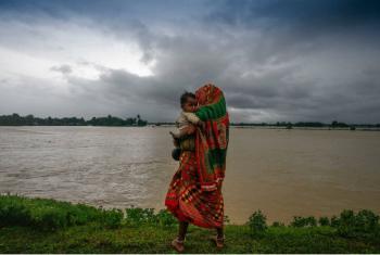 Deslocados pelas enchentes, uma mulher e seu filho caminham em uma estrada no sul do Nepal. Foto: Unicef Nepal/NShrestha