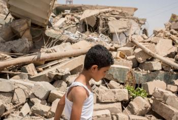 Menino passa em frente a casas destruídas no bairro de Al-Resala, na região oeste de Mossul, no Iraque. Foto: Acnur/Cengiz Yar