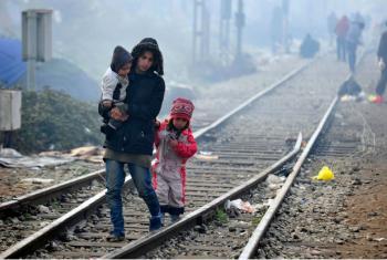 Ao longo dos trilhos de trem ligando a Grécia com a ex-República Iugoslava da Macedônia, uma mulher caminha com duas crianças. Foto: Unicef/Georgiev