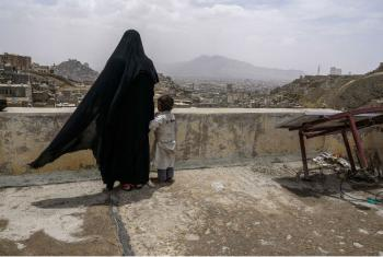 Uma mulher deslocada internamente e sua filha olham a cidade de Sanaa, no Iémen, a partir do telhado do prédio onde está abrigada. Foto: Giles Clarke/ Ocha.