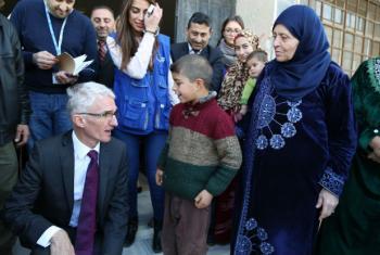 Mark Lowcock conversa com um menino em uma escola em Homs, na Síria. Foto: Ocha/Ghalia Seifo