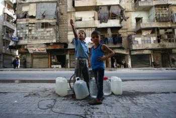 Meninos em Alepo, Síria, esperam para receber água. Foto: UNICEF/Zayat