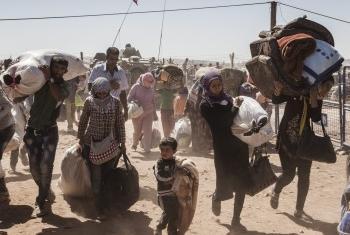 Беженцы из Сирии пересекают границу Турции. Фото УВКБ/И.Прикетт
