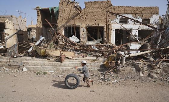 Mvulana mdogo anaendesha tai yake karibu na jengo lililoharibiwa na mikombora huko Saada Yemen. File: OCHA / G.Clarke