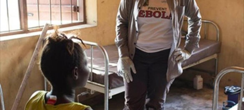 Mhudumu wa afya anazungumza na mama amekuwa katika mazingira ya watu waliokufa kutokana na Ebola nchini Sierra Leone.(Picha ya WHO/C.Black)