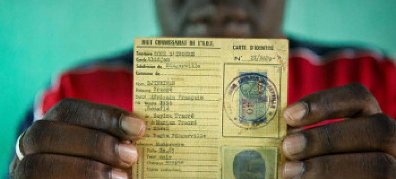 Oumar ambaye alikuwa hatarini kukosa utaifa, anaonyesha kitambulisho cha baba yake kutoka wakati wa ukoloni wa Ufaransa. Picha: UNHCR / Hélène Caux
