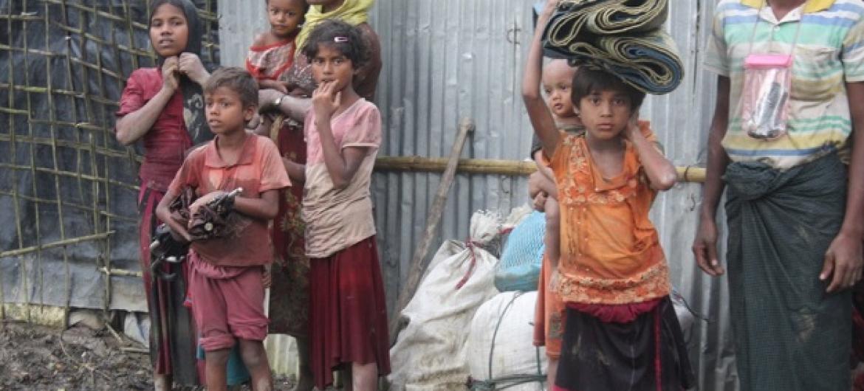 Familia geni ya wakimbizi kutoka Myanmar wanasimama kwenye matope nje ya kambi ya wakimbizi ya Kutupalong. Picha:UNHCR