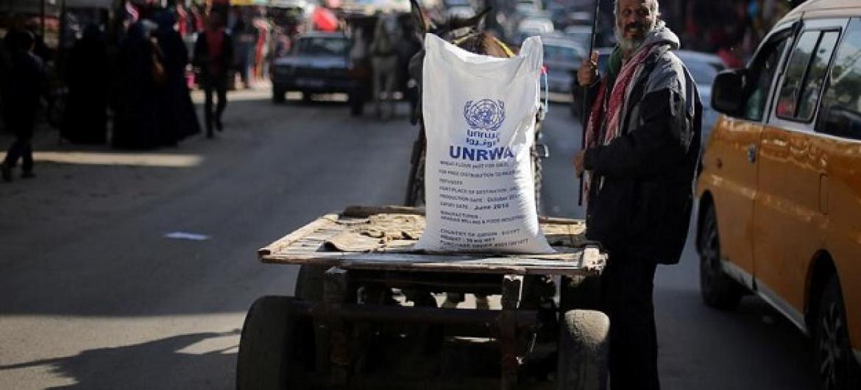 MPalestina akisimama karibu na gunia la unga iliyotolewa UNRWA katika kambi ya wakimbizi ya Khan Younis kusini mwa Gaza. Picha: UNRWA