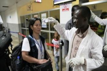 Uwanja wa ndege wa Lugin nchni Sierra Leone, mtaalamu wa afya kutoka WHO akipima joto la abiria ikiwa ni harakati za kudhibiti Ebola. (Picha:WHO-Sierra Leone)