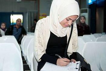 Mkimibizi Fatima akijaza fomu katika ofisi za UNHCR/Damascus(Picha© UNHCR/B.Diab)
