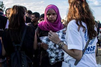 Mfanyakazi wa UNHCR akigawa blanketi kwa watu wanaosubiri kuvuka mpaka wa Ugiriki kwenye jamhuri ya zamani ya Yugoslavia, Macedonia. (Picha:UNHCR/A.Kitidi)