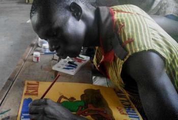 Mkimbizi akichora sanaa baada ya warsha iliyoendeshwa na Victor Ndula na Shirika la FilmAid International.