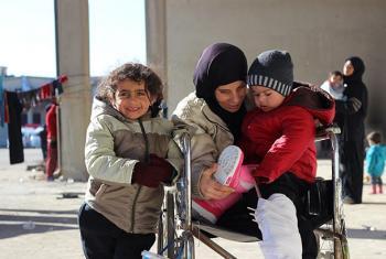 Watoto Rahaaf na Wael wavalishwa nguo mpya ya baridi na mama yao mashariki mwa Aleppo. Picha: UNICEF Syrian Arab Republic/2016/Al-Issa