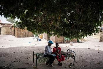 Mfanya kazi wa UNICEF Judy Jurua Michael (kushoto) anamhudumia mtoto akiwa na mamake Iman Diing. Picha; UNICEF/UN056592/Knowles-Coursin