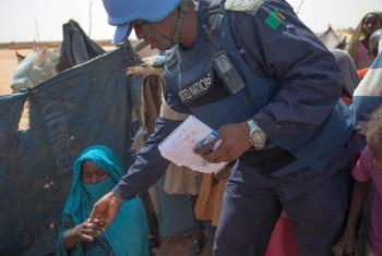 Mlinda amani wa UNAMID aizungumza na mama wakati akipiga doria katika kambi ya Zam Zam karibu na El Fasher, Darfur Kaskazini.(Picha:UNAMID/Hamid Abdulsalam)