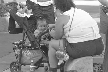Wengine wakiwa wamesimama karibu, mtoto analishwa na mamaye katika uwanja wa michezo ya watoto Disney World huko Orlando, Florida, nchini Marekani. Utipwatipwa ni tatizo kubwa nchini humo. Picha: UNICEF/Toutounji