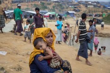Zulkhair, mwenye umri wa miaka 27, anabeba mtoto wake wa miezi 10, Mohammad, kambini Kutupalong. Mohammad ni mgonjwa na anahitaji matibabu. Picha: © UNHCR / Paula Bronstein