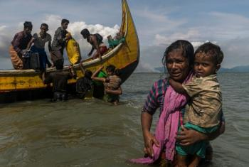 Mama akiwa amembeba mwanae wakati wakiwasili fukwe ya Dakhinpara, nchini Bangladesh wakitokea Myanmar. © UNHCR/Adam Dean